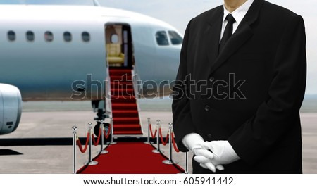 Man in black suits waiting next to private jet before departure