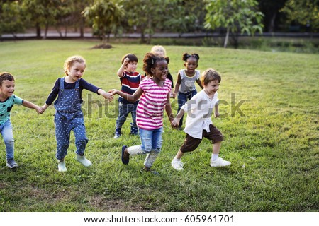 Happiness group of cute and adorable children playing in the park #605961701