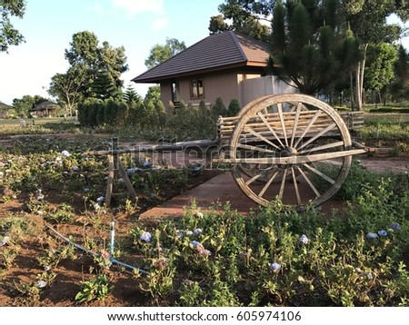 Brown cart is in front of a house. #605974106