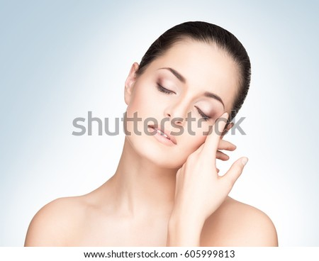 Portrait of young, beautiful and healthy woman: over blue background. Healthcare, spa, makeup and face lifting concept. #605999813