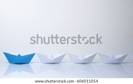 Leadership concept. Blue paper boat leading among white ships. Set of origami boats. Winner red paper ship on white background #606011054