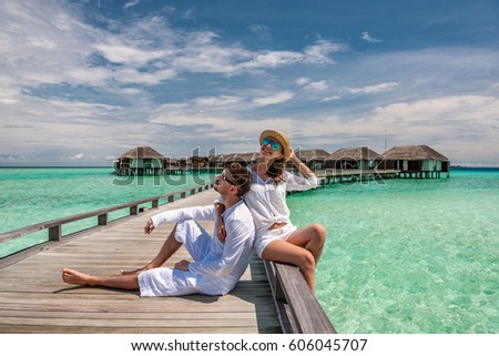 Couple in white on a tropical beach jetty at Maldives #606045707