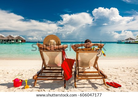 Couple in loungers on a tropical beach at Maldives #606047177
