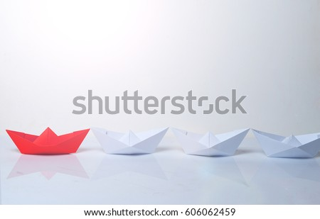 Leadership concept. Red paper boat leading among white ships. Set of origami boats. Winner red paper ship on white background. #606062459