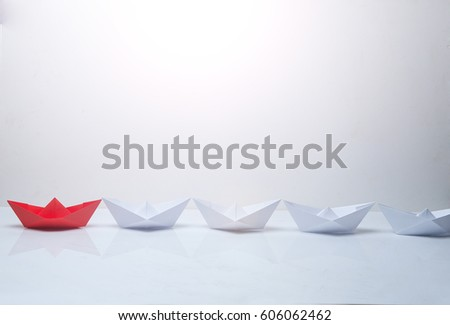 Leadership concept. Red paper boat leading among white ships. Set of origami boats. Winner red paper ship on white background. #606062462