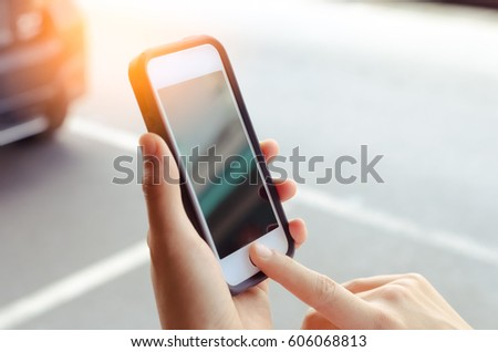 Copy space woman hand using smart phone and sun light on street background. Travel adventure lifestyle and business economic concept. Shallow depth of field. Vintage tone filter effect color style. #606068813