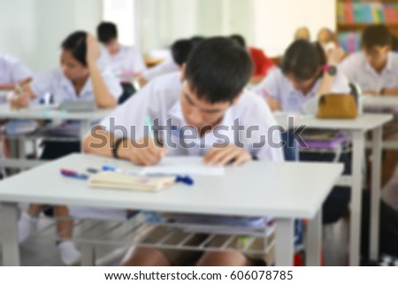 Student hand holding pen writing doing examination with blurred abstract background high school students in uniform attending exam classroom educational school: Blurry view people in class room #606078785