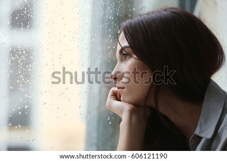 Depressed young woman near window at home, closeup Royalty-Free Stock Photo #606121190