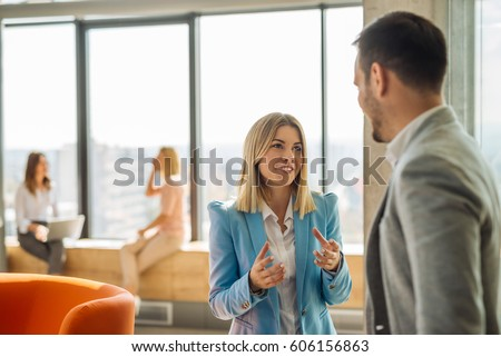 Photo of two colleagues discussing about the project in the office. Royalty-Free Stock Photo #606156863