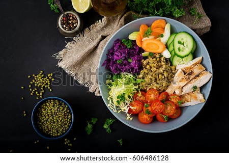 Healthy salad with chicken, tomatoes,  cucumber, lettuce, carrot, celery, red cabbage and  mung bean on dark background. Proper nutrition. Dietary menu. Flat lay. Top view Royalty-Free Stock Photo #606486128