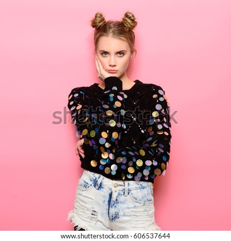 Beautiful hipster thinking girl with pigtails wearing funny sweater and jeans posing on pink background