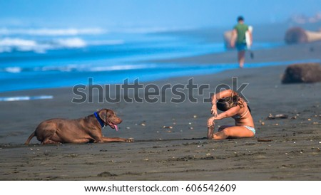 Yoga exercises on the beach. The dog watches with curiosity #606542609