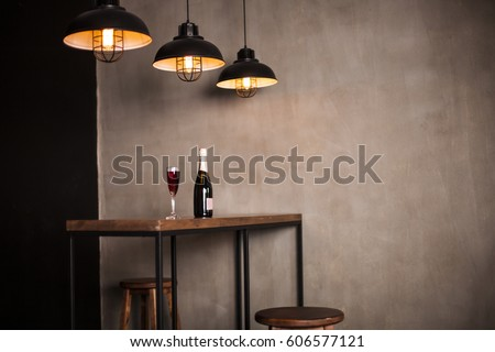 Interior photography. A bottle of wine and a glass stand on a wooden table in the restaurant hall.