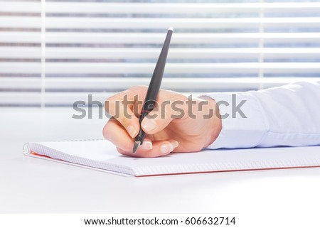 Hand making notes on the ring-bound notebook #606632714
