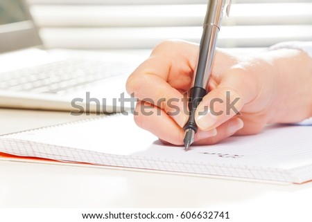 Female hand with fountain pen writing on notebook #606632741