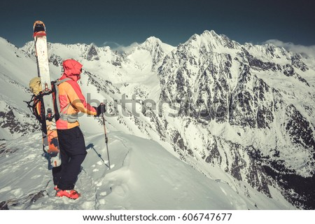 Vintage photo of Extreme backcountry skier at the summit, mountain top watching around with fat skis on his avalanche backpack, danger, sunny, mood, crazy as lifestyle adrenaline winter sport