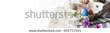 Easter Painted Eggs Delicate Composition with Fresh Wild Flowers in Metal Wicker Basket in Kinfolk Rustic Style #606755561