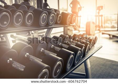Rows of dumbbells in the gym with hign contrast and monochrome color tone #606762704