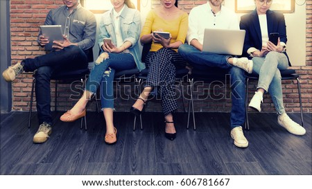 Multiethnic asian business group in casual suit using smart phone, tablet and laptop for working or playing social network and web site in modern office. Business and Technology concept Royalty-Free Stock Photo #606781667