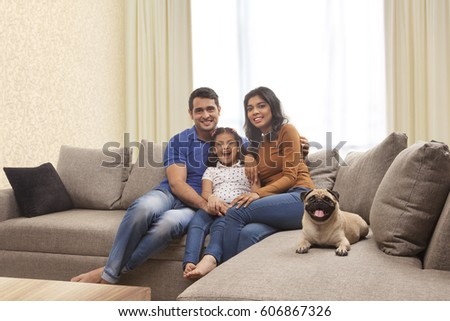 Portrait of smiling family with daughter and pug sitting on sofa  #606867326