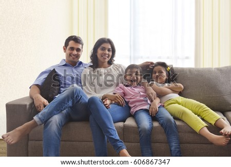 Portrait of family relaxing on sofa together  #606867347