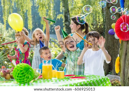 Children with party hats and trumpets during garden party #606925013