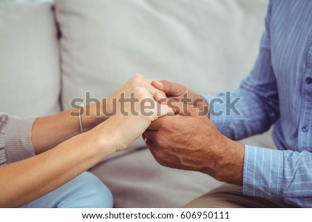 Close-up of man and woman holding hands at home #606950111