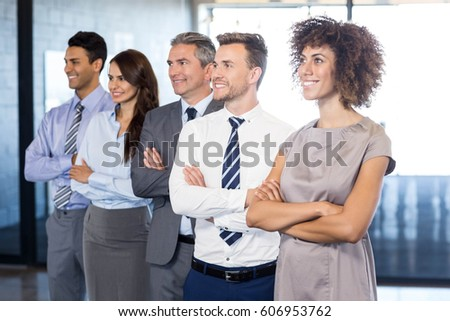 Confident business team standing in office with their hands crossed #606953762