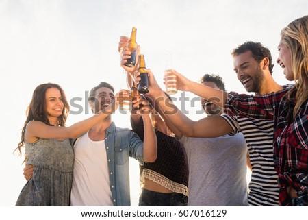 Happy friends raising beer bottles on the beach #607016129