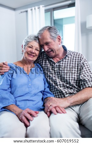 Happy senior couple sitting on sofa and embracing in living room #607019552