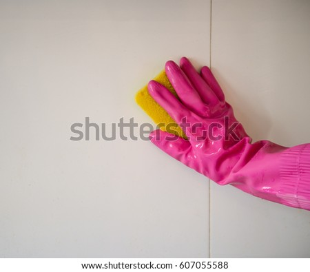 Hand with sponge cleaning the bathroom tiles. #607055588