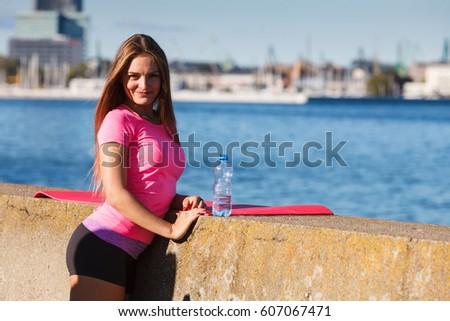 Woman in sportswear takes a break to rehydrate drinking water from plastic bottle, resting after sport workout outdoor by seaside #607067471