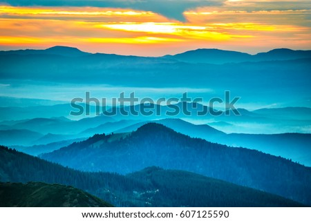Sunset in the mountains. Dramatic colorful clouds over blue hills #607125590