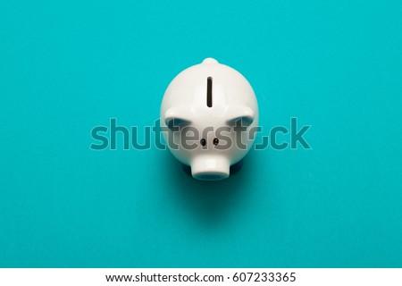 Piggy bank isolated on aquamarine  background  Royalty-Free Stock Photo #607233365