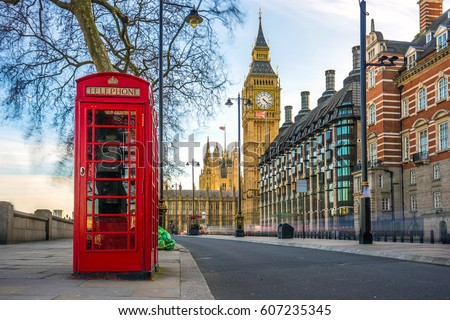 London, England - The iconic british old red telephone box with the Big Ben at background in the center of London Royalty-Free Stock Photo #607235345