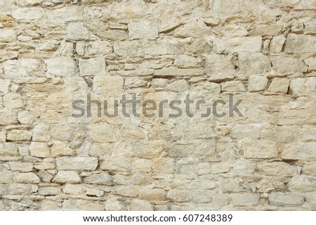 Old beige stone wall background texture close up #607248389