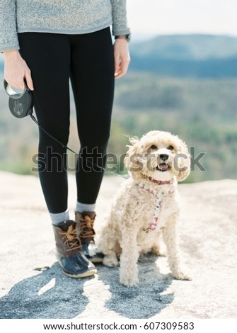 Woman Stands with a Small White Dog #607309583