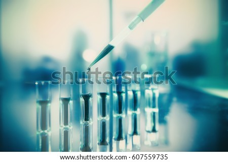 Scientific background, protein analysis. Spectrophotometer quvettes on a reflective surface, copy space. Focus on the pipette tip. This image is toned. #607559735