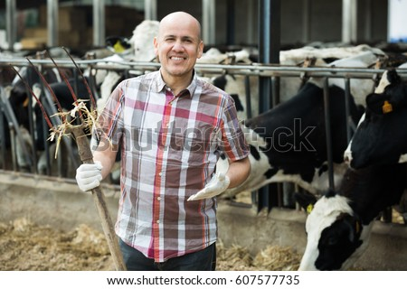 Positive worker posing with pitchfork in cows barn #607577735