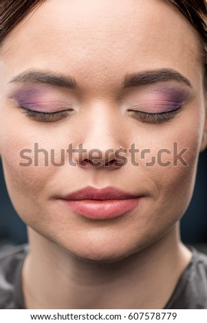 Close-up portrait of young woman with glamorous make-up with closed eyes #607578779