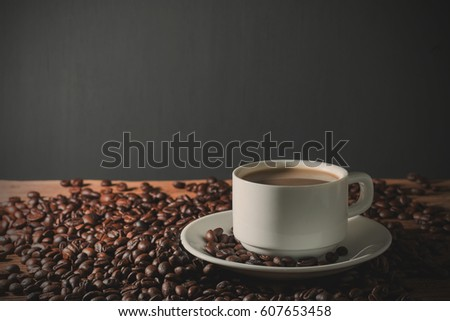 Coffee cup and coffee beans on table wood black background. with copy space for text. #607653458