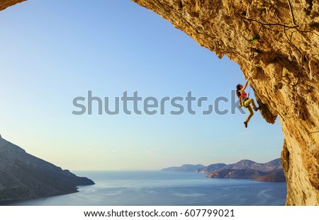Young woman climbing challenging route in cave at sunset Royalty-Free Stock Photo #607799021