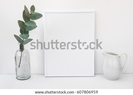White frame mockup, eucalyptus branch in glass bottle, pitcher, styled minimalist clean image for product marketing, social media, blogging #607806959