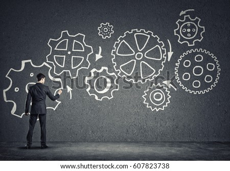 Businessman standing with back and drawing concept of teamwork and cooperation #607823738