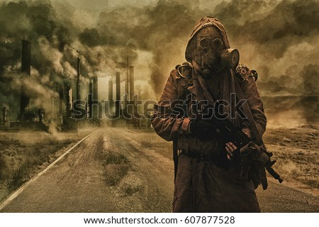 Post-apocalyptic air pollution. Survivor in tatters and gas mask on the background of pipes on abandoned road. Nature protection concept #607877528