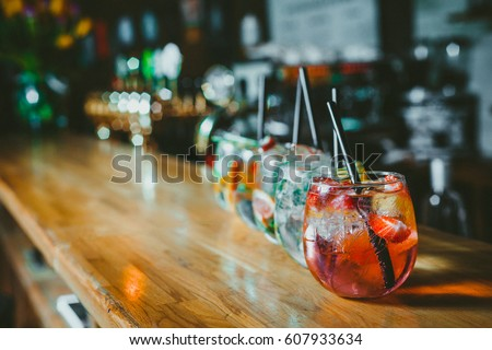 Alcoholic cocktail row on bar table, colorful party drinks  Royalty-Free Stock Photo #607933634