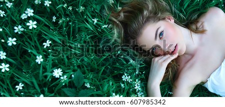Beautiful young girl lies on a clearing among white flowers. White flowers. Chamomile. A girl with her hair in a white dress. #607985342