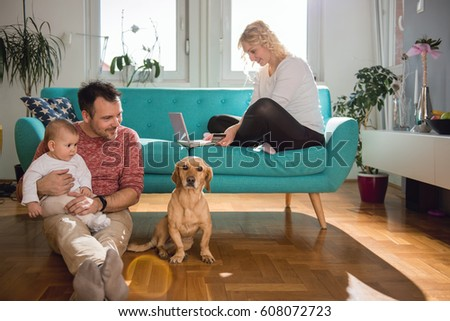 Father sitting on the floor and with baby in his arms playing with dog while wife sitting on sofa and doing online shopping with credit card #608072723