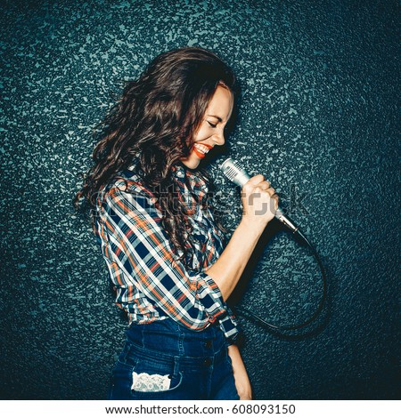 Crazy girl holding microphone and smiling. Attractive Beautiful curly brunette young woman singing studio. Close up portrait Royalty-Free Stock Photo #608093150