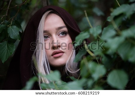 Cute blond teen with nice big lips and beautiful green eyes surrounded by green leaves #608219219